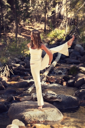 Woman in yoga posture outdoors in a forest stream  photo