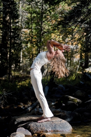 Semi silhouette of Woman in yoga pose outdoors in the wods