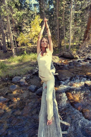 Woman in yoga posture outdoors in the forest   photo