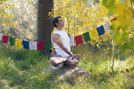Man in yoga posture outdoors in the forest   Stock Photo - 17162543