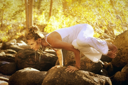 aging: Woman in yoga posture outdoors in the forest