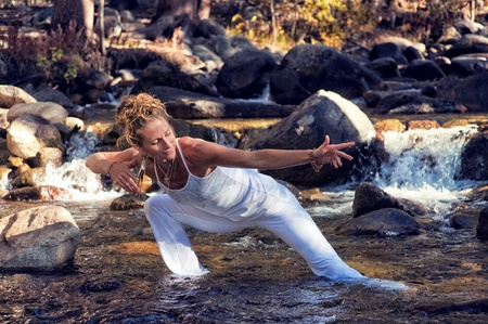 aging brain: Woman in yoga posture outdoors in a forest river  Stock Photo