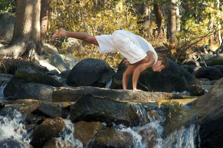 Man in yoga posture outdoors in a forest mountain river Stock Photo - 17162463