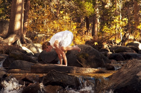 Man in yoga posture outdoors in a forest mountain river  Stock Photo - 17162515