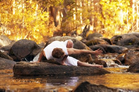 Man in yoga posture outdoors in a forest mountain river  photo