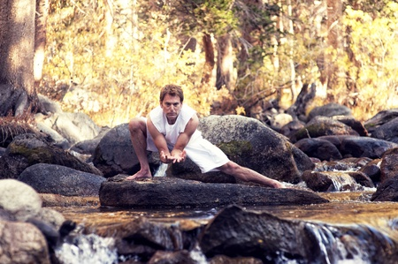 Man in yoga posture outdoors in a forest mountain river  Stock Photo
