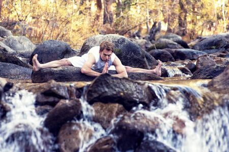 prana: Man in yoga posture outdoors in a forest mountain river  Stock Photo
