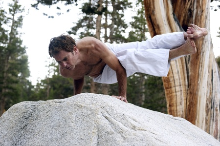 Man in dynamic expression of yoga pose outdoors in the woods