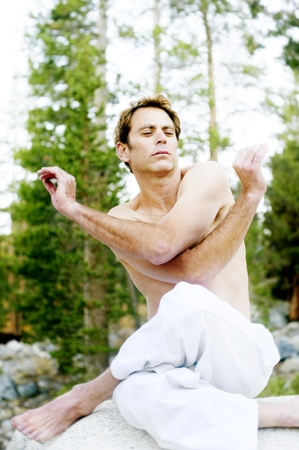 prana: Man in dynamic expression of yoga mudra outdoors in the woods  Stock Photo