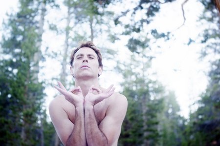 Man in yoga posture outdoors in the forest   photo