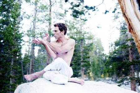 Man in dynamic yoga mudra gesture outdoors in the woods