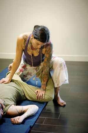 bodywork: Thai yoga therapist working on her client