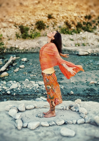 Woman outdoors near a river with her arms and heart open in a mandala of stones