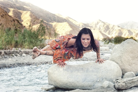 Woman outdoors in yoga pose astavakrasana in the mountains near a river   Stock Photo - 17162487