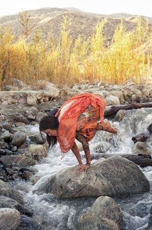 Woman outdoors in yoga pose bakasana in a mountain river