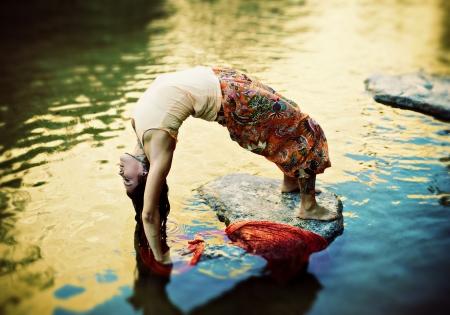 Yoga Woman outdoors in yoga pose urdhva dhanurasana in a colorful pond