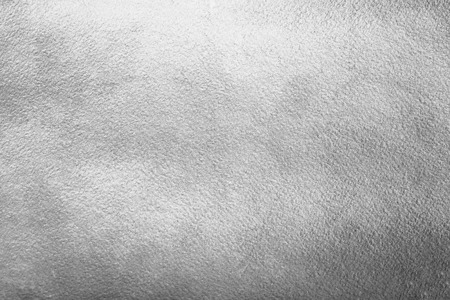 Silver or iron background. Rough metal texture. Silver or steel paper template for your design. Silver foil monochrome background. Industrial texture.
