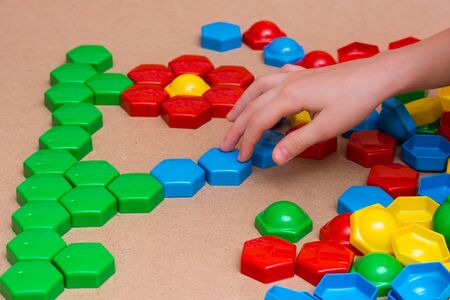 Child's hands add colored mosaic details to the drawing on the table. Leisure of the child in confinement. Table game