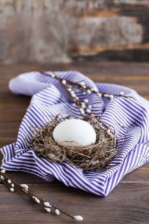 Happy easter. One unpainted chicken egg in a bird's nest and willow branches on a wooden table. The concept of rejection of dyes in food. Copy space