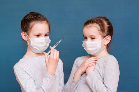 Girls in medical masks look at a syringe with medicine in their hands and are afraid. Vaccination, treatment of children. Outbreak Prevention Banque d'images