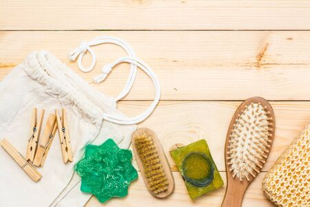 Zero waste bathroom accessories, natural sisal brush, wooden comb, solid soap, canvas bag and wooden clothespins on a natural wooden background. Top view