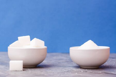 Sugar cubes and granulated sugar in white bowls on a table against a blue background. Concept
