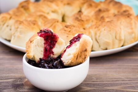 Pull apart monkey bread with black currant jam in a plate on a wooden plate