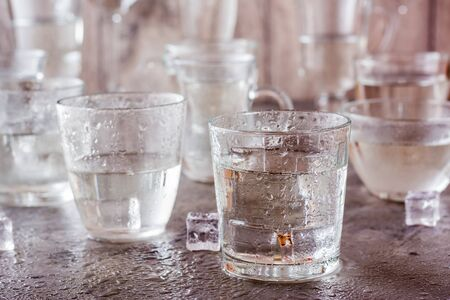 Many glasses of water splashed with drops and pieces of ice on a gray background
