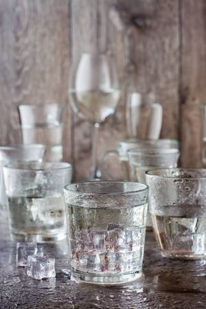 Many glasses of water splashed with drops and pieces of ice on a gray table Imagens