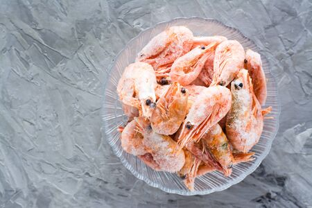 Group of frozen shrimp in a glass bowl on a gray table. Top view