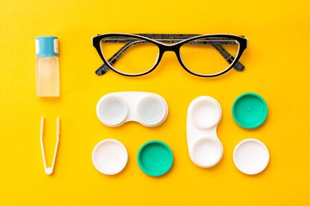 Accessories for storing lenses: a bottle of liquid, open containers and tweezers, glasses on a yellow background. Top view Stock Photo