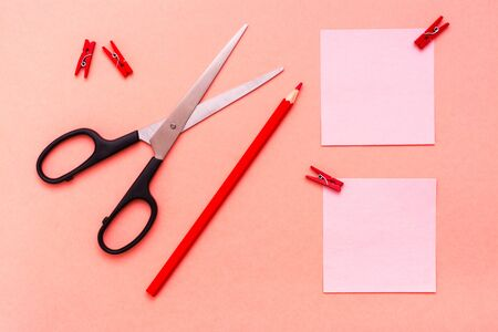 Stationery - sheets for notes clipped, pencil and scissors on a red background. Top View