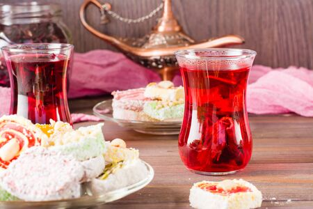 Hot karkade in cups and Turkish Delight on a plate on a wooden table