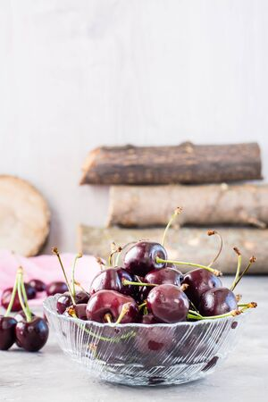 Ripe fresh sweet cherries  in a glass bowl on a gray background