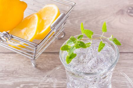 Refreshing mineral water with ice cubes and mint leaves in a transparent glass and lemon slices in a basket on a wooden table