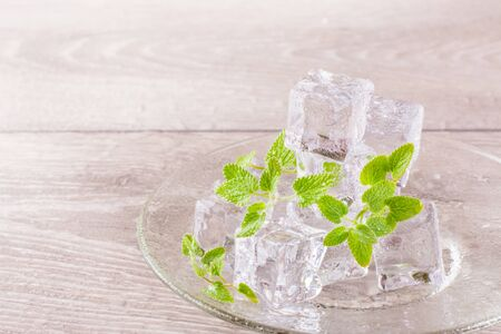 Melting ice cubes and mint leaves on a saucer on a wooden table