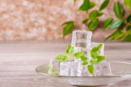 Melting ice cubes and mint leaves on a saucer on a wooden table Stock Photo