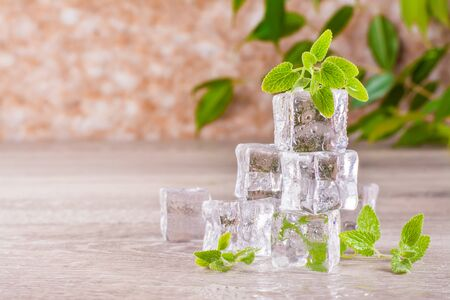 Melting ice cubes and mint leaves on a wooden table Reklamní fotografie