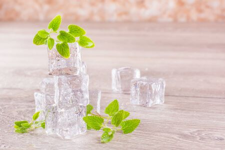 Melting ice cubes and mint leaves in droplets of water on a wooden table