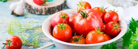 Ripe tomatoes in a plate and herbs on a wooden table.