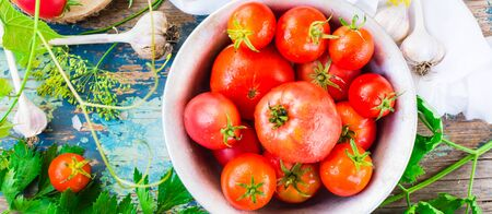 Ripe tomatoes in a plate and herbs on a wooden table. Top view