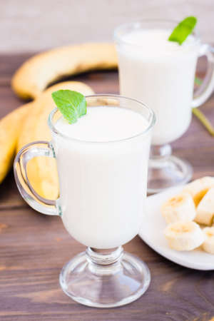 Banana smoothie with mint leaves in glasses on a wooden table