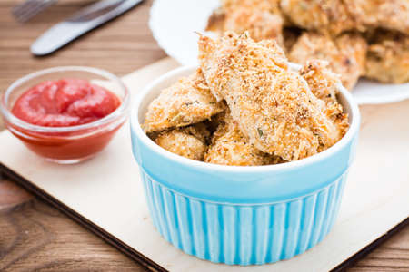 Homemade nuggets from chicken in a bowl and on a plate  on a wooden table Stockfoto