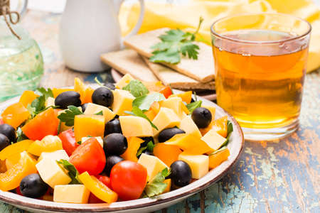 Greek salad with fresh vegetables and glass of juice on a wooden table