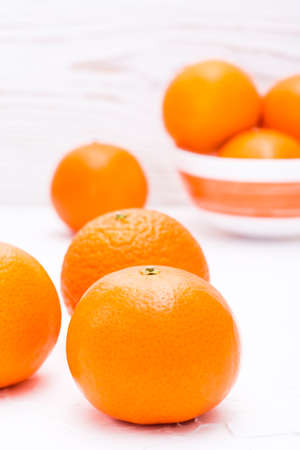 Ripe mandarins on a table and in a bowl