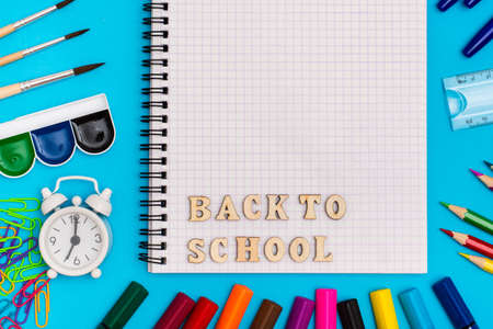 Back to school. Stationery, alarm clock and inscription in wooden letters in a notebook on a blue background. Top view. Copy space Foto de archivo