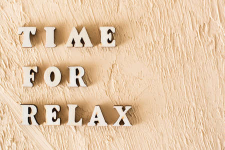 Time for relax. Text from wooden letters on textured beige plaster background Archivio Fotografico