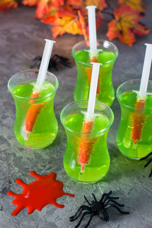 Halloween cocktails. Syringes with blood in glasses with green lemonade and spiders on the table. Vertical view. Copy space