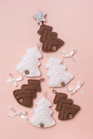 Christmas handmade. Knitted fir-trees with decor are laid out in a triangle on a pastel background. Handicraft and leisure. Vertical view
