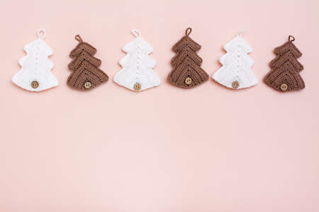 Christmas handmade. Knitted fir-trees in a row on a pastel background. Handicraft and leisure. Copy space Stock Photo